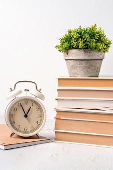 Bureau met wekker en een stapel boeken en groene plant. concept tijd om te werken
