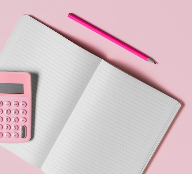 Bureau minimaal leeg notitieboekje en roze rekenmachine