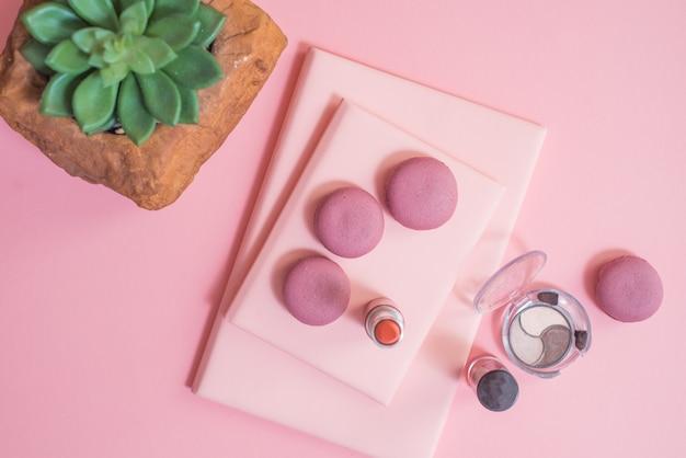 Bureau op roze glazen kladblok schoppen potloden plant bitterkoekjes wekker bovenaanzicht