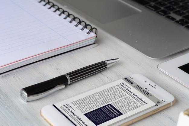 Bureau tafel met computer, tablet, benodigdheden en breaking news op smartphone