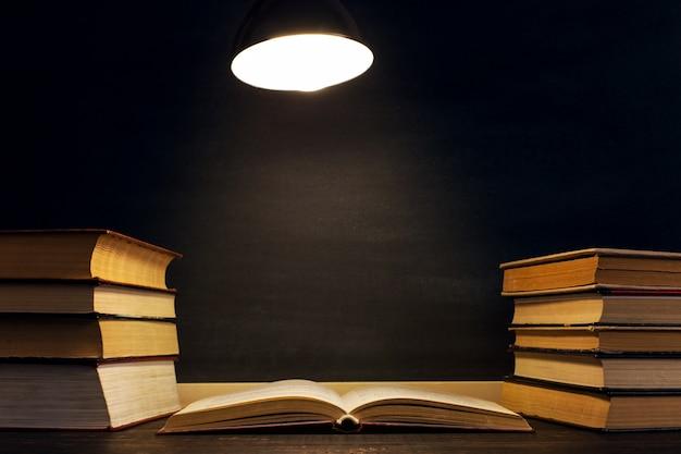 Bureau tegen de achtergrond van het schoolbord, boeken in het donker onder het licht van een lamp.