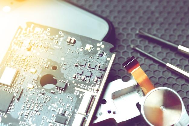 Bureau voor reparatie van elektronische apparatuur op donkere achtergrond met kopie ruimte, elektronische reparatie elektronica concept
