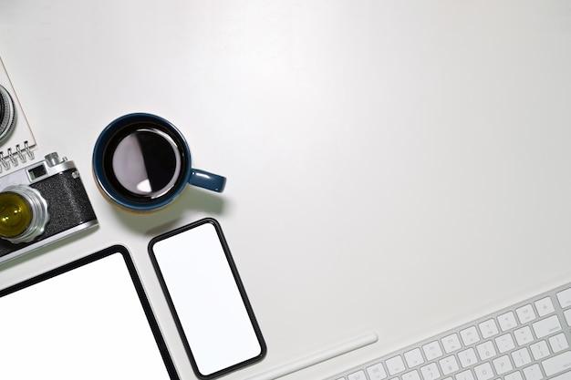 Bureau wit bureau met lege schermtablet, uitstekende camera, koffiemok en exemplaarruimte