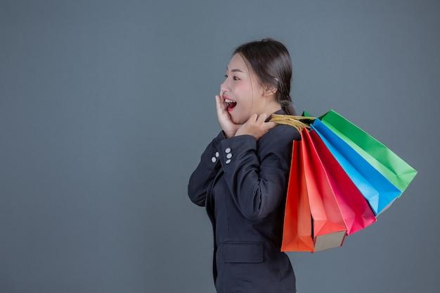 Bureaudame die een manier het winkelen zak houdt