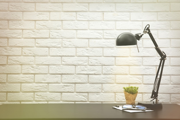 Bureaulamp op het bureau op bakstenen muurachtergrond