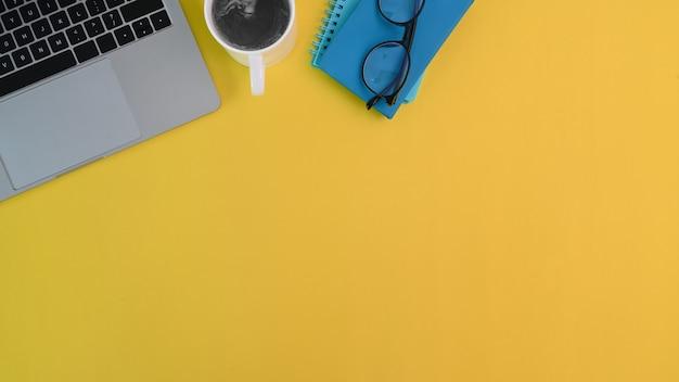 Bureaulaptop, koffie, notitieboekje en glazen op geel bureau met exemplaarruimte.