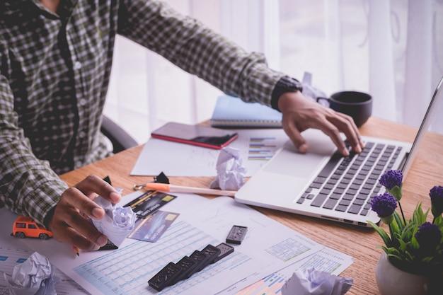 Bureaulijst met bezige zakenman die laptop met behulp van, bezig bureau in huisbureau.