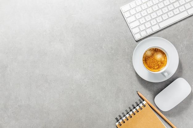 Bureaulijst met kop van koffie, toetsenbord en blocnote