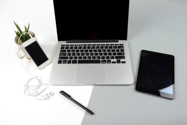 Bureaulijst met laptop computer, notitieboekje, digitale tablet en mobiele telefoon op twee toon b