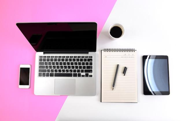 Bureaulijst met laptop computer, notitieboekje, digitale tablet en smartphone op twee toonbedelaars