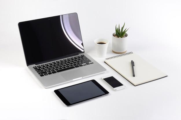Bureaulijst met laptop computer, notitieboekje, digitale tablet en smartphone op witte achtergrond.