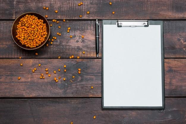 Bureaulijst met notitieboekjes, verse wegedoornbessen op houten lijst