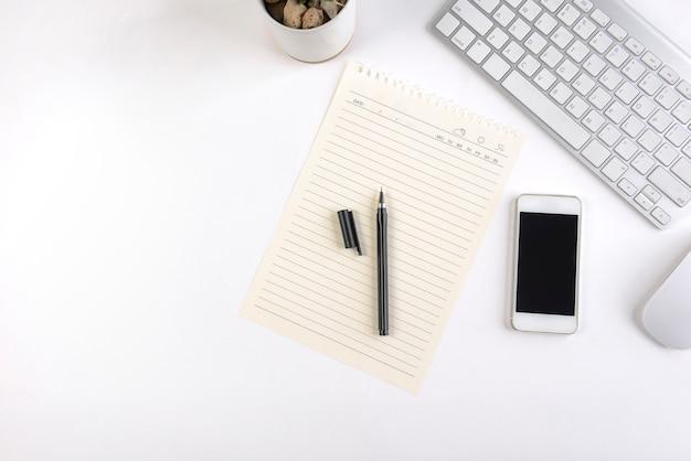 Bureaulijst met toetsenbord, muis, notitieboekje en smartphone op witte achtergrond.