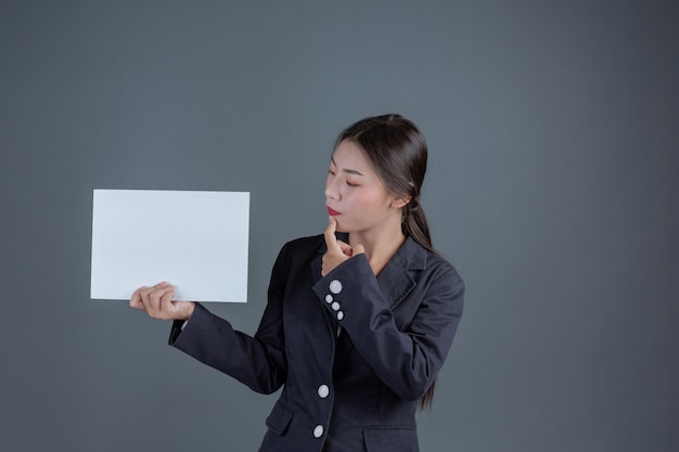 Bureaumeisje die een witte lege raad houden