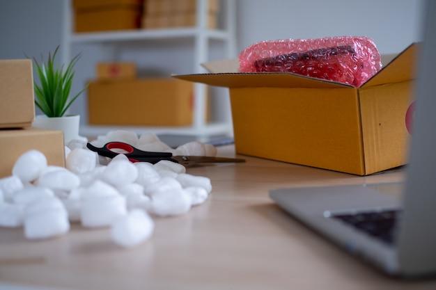 Bureaus voor kleine bedrijven in online verkoop, kartonnen pakketdozen met producten voor levering aan klanten.