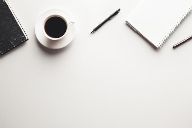 Bureautafel met benodigdheden, koffiekopje en bloem. bovenaanzicht met kopie ruimte