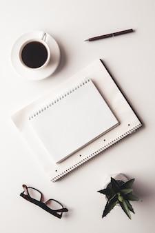 Bureautafel met benodigdheden, koffiekopje en bloem. bovenaanzicht met kopieerruimte