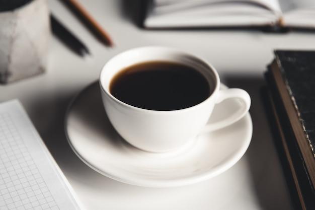 Bureautafel met benodigdheden, koffiekopje en bloem