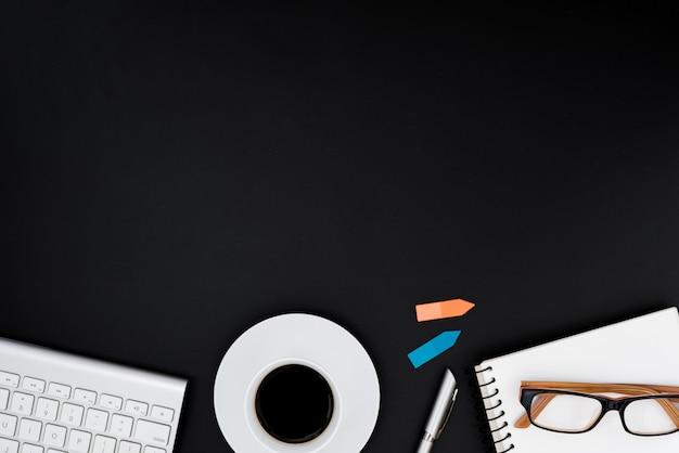 Bureautafel met computer, lenzenvloeistof, zilveren pen, blauwe en oranje post-it en koffiekopje. de bovenkantmening van de bedrijfsbureautafel met copyspaceconcept.