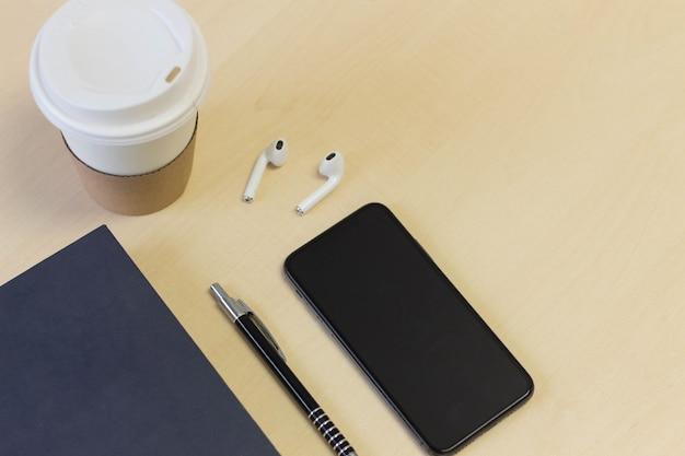 Bureautafel met een kopje koffie, smartphone, boek en een koptelefoon