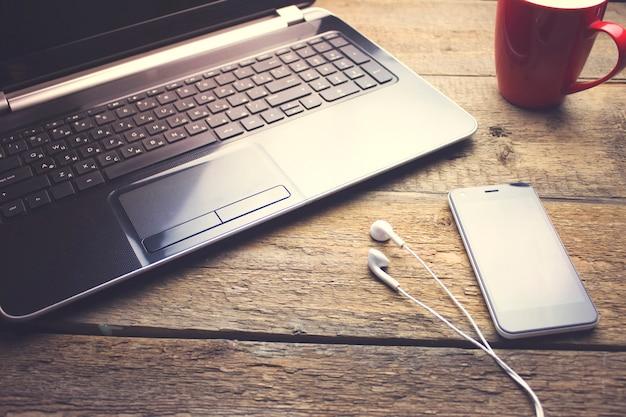 Bureautafel met koffiekopje, computer, smartphone en koptelefoon