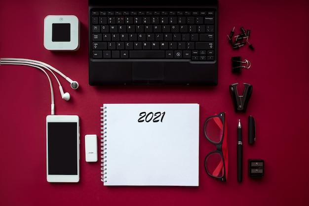 Bureautafel met labtopcomputer, smartphone en notebook met tekst 2021. bovenaanzicht witte tafel met kopieerruimte.