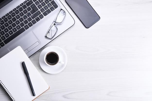 Bureautafel met laptop, slimme telefoon, kopje koffie en benodigdheden, op houten