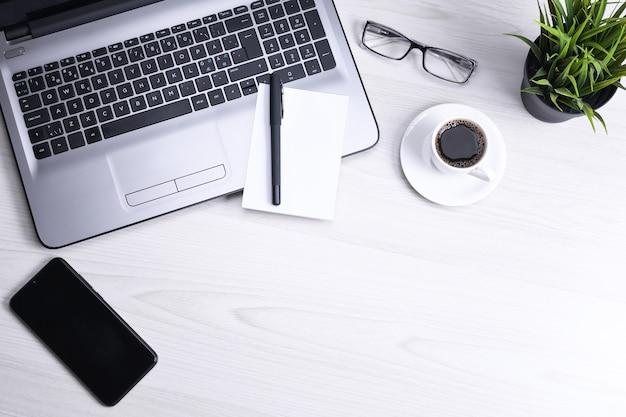 Bureautafel met laptop, slimme telefoon, kopje koffie en leveringen, op houten achtergrond. bovenaanzicht met kopie ruimte, plat leggen.