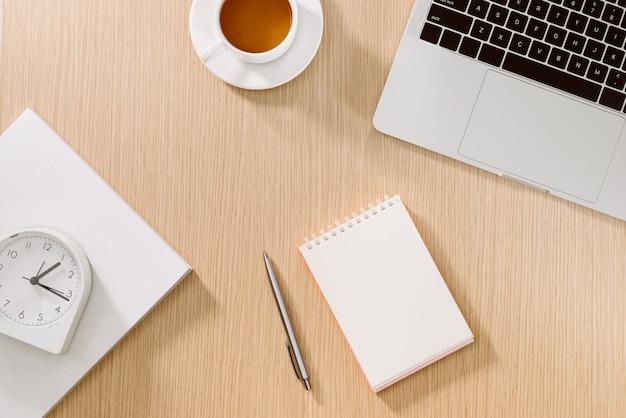 Bureautafel met laptop, smartphone, kopje koffie, pen, potlood en notitieboekje. kantoorbenodigdheden en gadgets op bureautafel. bureau tafel concept.