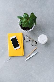 Bureautafel met notebookplanner, smartphone, bril, koffieboom en koffiekopje. bovenaanzicht met kopie ruimte.
