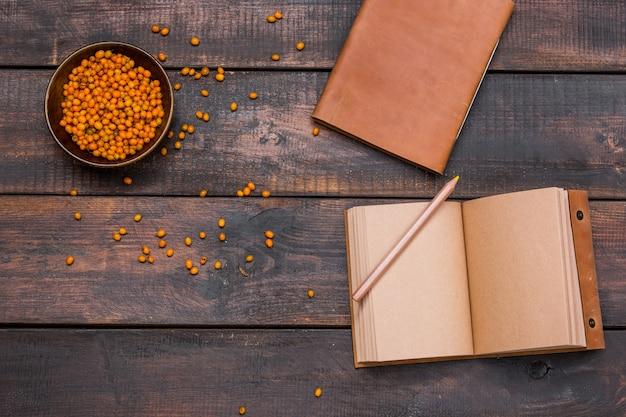 Bureautafel met notitieboekjes, verse duindoornbessen op houten lijst