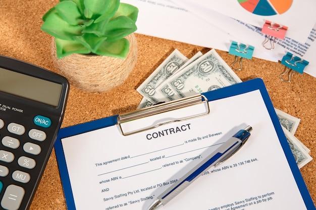 Bureautafel, rekenmachine, pen en documenten met contractspatie