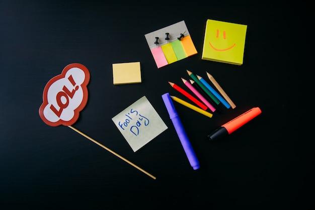 Bureautoebehoren op zwarte achtergrond. teken op een stok. plaknotities, stift, kleurpotlood.