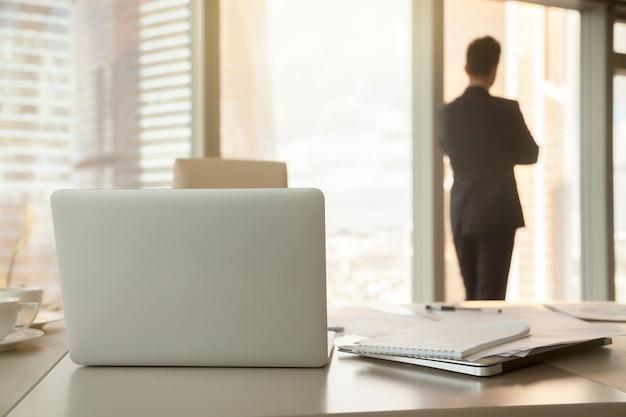 Bureauwerkplaats met laptops en documenten, mannelijk silhouet bij