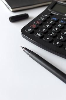 Bureauwerkplaats met tekst ruimte, zwart boek en calculator op witte lijst