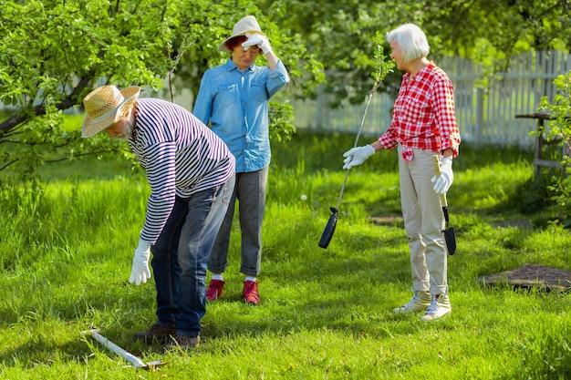 Buren houden van de natuur. drie vriendelijke actieve buren die van de groene natuur houden en bomen planten in de buurt van huizen