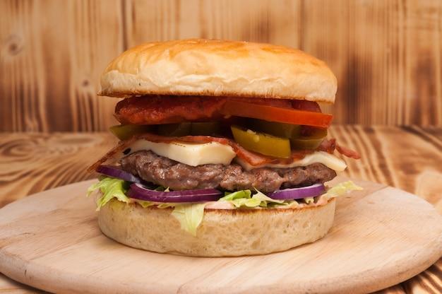 Burger met runderpasteitje, bacon, jalapeno, kaas, tomaat en ui