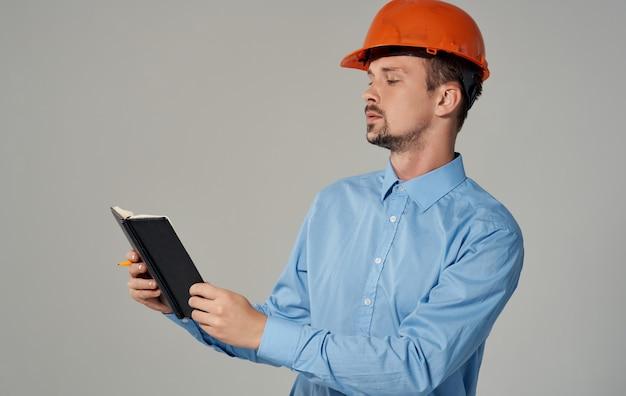 Burgerlijk ingenieur in de oranje documenten van de bouwvakkerholding in handen kladblok bedrijfswerk.