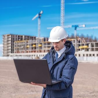Burgerlijk ingenieur in een witte helm op zoek naar documenten over de bouw
