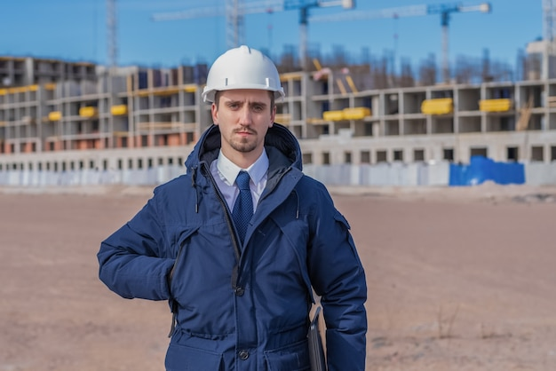 Burgerlijk ingenieur in een witte helm, winterjas op de gebouwen in aanbouw.
