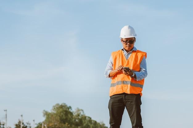 Burgerlijk ingenieur op de bouwplaats met behulp van smartphone controleren of contact opnemen met het werk. beheer op de bouwplaats.