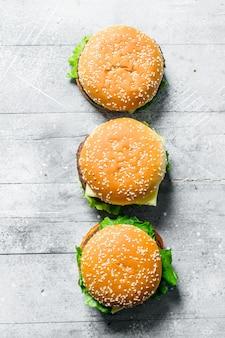 Burgers met rundvlees, groenten en kaas. op witte houten achtergrond