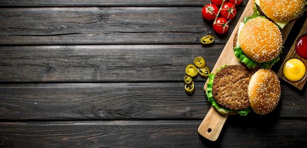 Burgers met verschillende sauzen, jalapenos en tomaten. op zwarte houten achtergrond