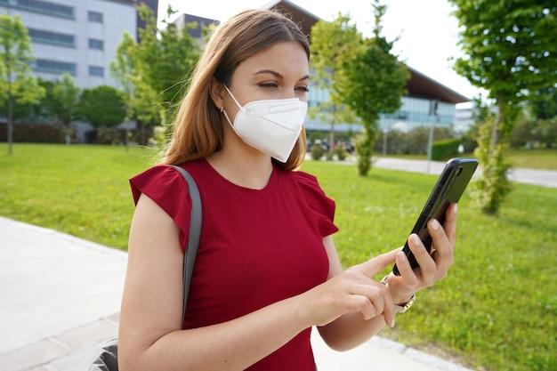 Burgervrouw met medisch masker die buiten naar haar mobiele telefoon kijkt. groene pas en digitaal covid-certificaatconcept.