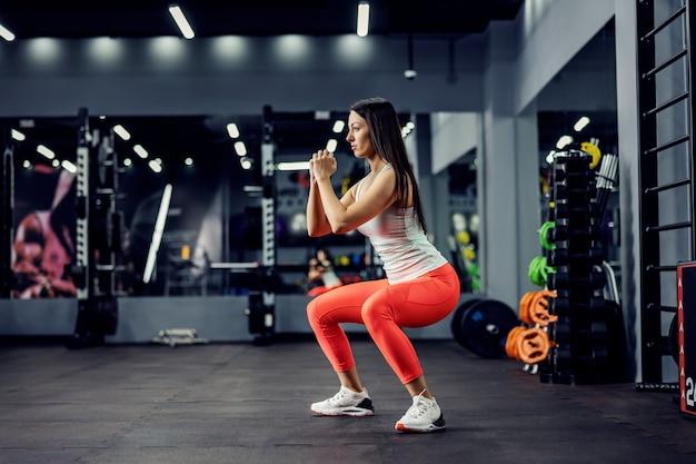 Burn-in billen. zijaanzicht van een jonge vrouw in sportkleding die een diepe kraakpand doet terwijl ze in het midden van de sportschool staat. fit zijn, calorieën verbranden