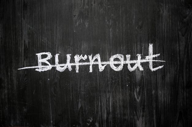 Burnoutwoord met de hand geschreven en doorgehaald op bord