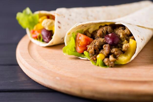 Burrito met rundvlees, kip, limoen, peper en groenten, op een houten bord.