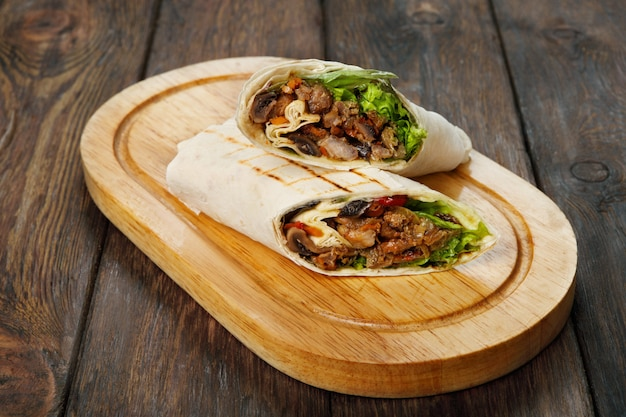 Burrito met varkensvlees en groenten op houten bureau