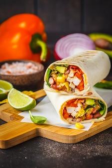 Burrito's wraps met kip, bonen, maïs, tomaten en avocado op een houten bord