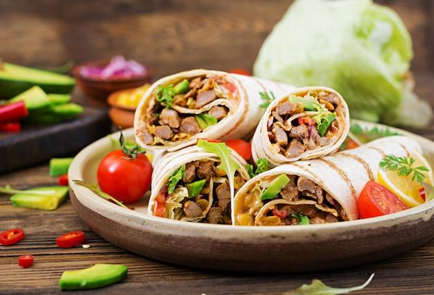 Burrito's wraps met rundvlees en groenten op een houten tafel. rundvlees burrito, mexicaans eten. mexicaanse keuken.